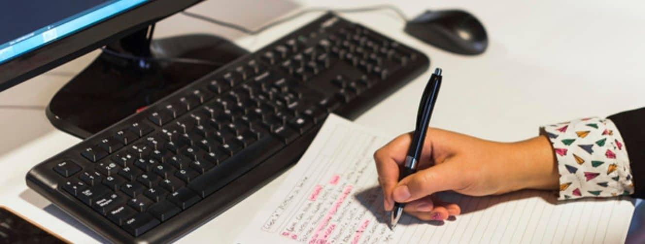 escrevendo no caderno na mesa do computador
