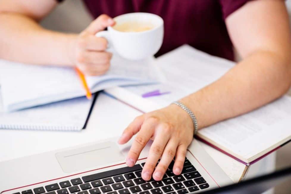 mãos sobre um notebook escrevendo