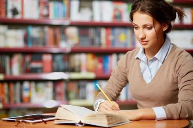mulher lendo e escrevendo em um livro